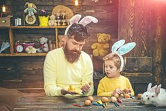 Child and father holding basket with painted eggs. stock photos