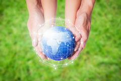 Child and father holding planet Earth in hands against green spring background. stock images