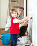 Child  with father paints wall Royalty Free Stock Image