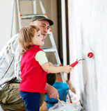 Child  with father paints wall Royalty Free Stock Images