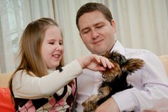 Child with father playing with dog Royalty Free Stock Images