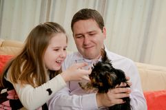 Child with father playing with dog Stock Image