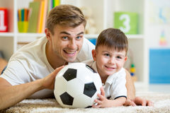 Child and father playing with football Royalty Free Stock Photos
