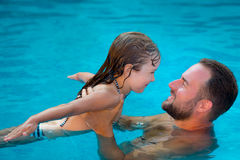 Child and father playing in swimming pool Royalty Free Stock Image