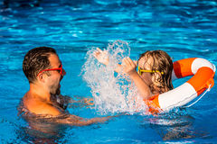 Child and father playing in swimming pool Royalty Free Stock Photos