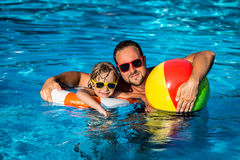 Child and father playing in swimming pool Royalty Free Stock Photography