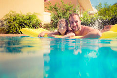 Child and father playing in swimming pool Stock Images
