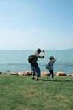 A child and the father throwing stones. Royalty Free Stock Photos