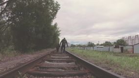 The child with the father walk on the railway tracks. The child with the father walk on the railway tracks stock video footage