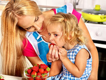 Child feed mother  at kitchen. Royalty Free Stock Photography