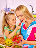 Child feed mother  at kitchen Royalty Free Stock Photo