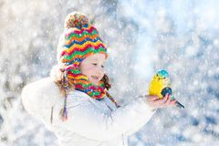 Child feeding bird in winter park. Kids play in snow. Nature and Stock Photo