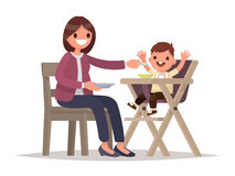 Child Feeding. Mother feeds the baby sitting in the highchair. V Royalty Free Stock Photo