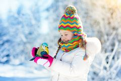 Child feeding bird in winter park. Kids play in snow. Nature and Stock Photos