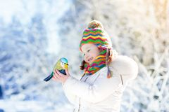Child feeding bird in winter park. Kids play in snow. Nature and Stock Images