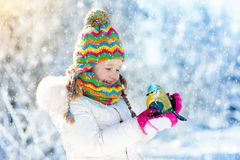 Child feeding bird in winter park. Kids play in snow. Nature and Royalty Free Stock Photos
