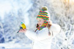Child feeding bird in winter park. Kids play in snow. Nature and Royalty Free Stock Images