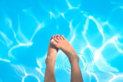 Child feet above the water in swimming pool Stock Photos