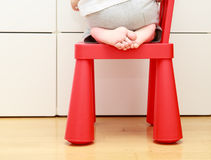 Child feet on baby chair, kids home safety concept. Child feet on baby chair, concept of danger, risk and parent responsibility Royalty Free Stock Photo