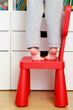 Child feet on baby chair, kids home safety concept. Child feet on baby chair, concept of danger, risk and parent responsibility Stock Photo