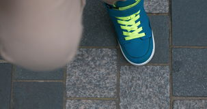 Child feet in blue trainers on sidewalk stock video