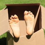 Child feet in box. Child bare feet of a little girl sticking from a paper box royalty free stock images