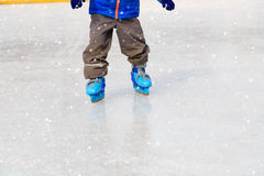 Child feet learning to skate on ice in winter Stock Photo