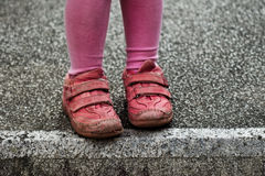 Child feet on old stone block. Child feet in red sneakers. Urchin style. Crossing a white line or edge. Contrast colors, close-up. Hesitating royalty free stock photo