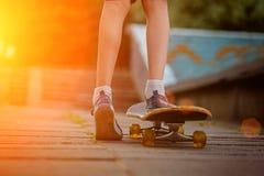 Child feet with skateboard on the street at sunset light Stock Photo