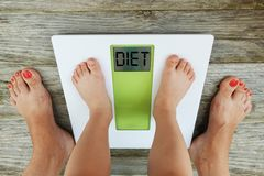 Child feet standing on digital weight scale in front of his mother, diet recommendation royalty free stock photo