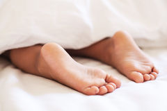 Child feet under the blanket. Royalty Free Stock Photo