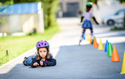 Child fell while learning to roller skate on the road. Royalty Free Stock Photography