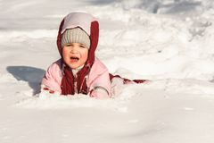 The kid fell into the snow and cries. The child fell into the snow and cries Stock Photo