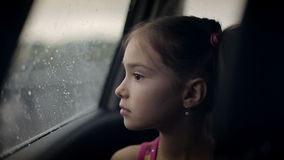Child female in the car in raining. stock footage