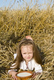 Child in a field. Portrait of a child lying in a field of wheat ears in national dress with a plate of milk Stock Images