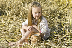 Child in a field. Child sitting on a the field of wheat ears in national dress with a milk's pitcher Royalty Free Stock Photography