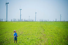 Child on the field with wind generators Royalty Free Stock Photo