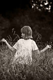 Child in the fields - BW. Long, tall, waist length & more, grass surrounds this adolescent girl. More action oriented Royalty Free Stock Photo