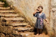 Child figurine in crib scene Stock Images