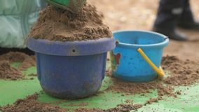 Child filling bucket with sand on table in sandbox. Close-up of hands of unknown child filling bucket with sand on green table in sandbox in an amusement park at stock footage