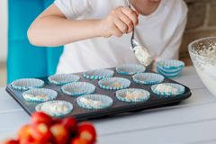 Child filling cupcakes form with dough ingredients Royalty Free Stock Photo