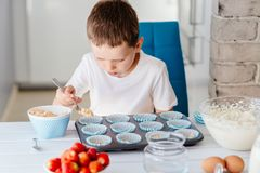 Child filling cupcakes form with dough ingredients. Boy helping in the kitchen. Baking with children stock images