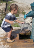 Child filling water bottle Royalty Free Stock Images