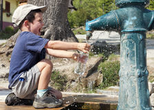 Child filling water bottle Stock Images