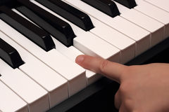 Child finger pressing white piano key Royalty Free Stock Photography