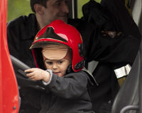 Child in a fireman's helmet in the Fire Truck. SZCZECIN, POLAND - MAY 29, 2014: Veterans Day in Poland. Child in a fireman's helmet.Boy playing with the steering Royalty Free Stock Photo