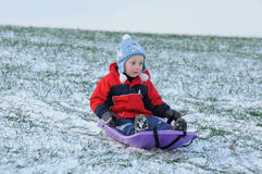 Child on first snow. Active little child sitting on violet sledge and sledging on first snow Royalty Free Stock Images