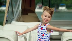The child the first time rides the boat. The girl in a lovely dress costs on the boat on water stock video footage