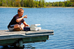 Child Fishing. Child selecting the right bait sitting on a dock Royalty Free Stock Image