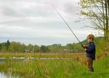 Child fishing. Young boy fishing at local pond Stock Photo